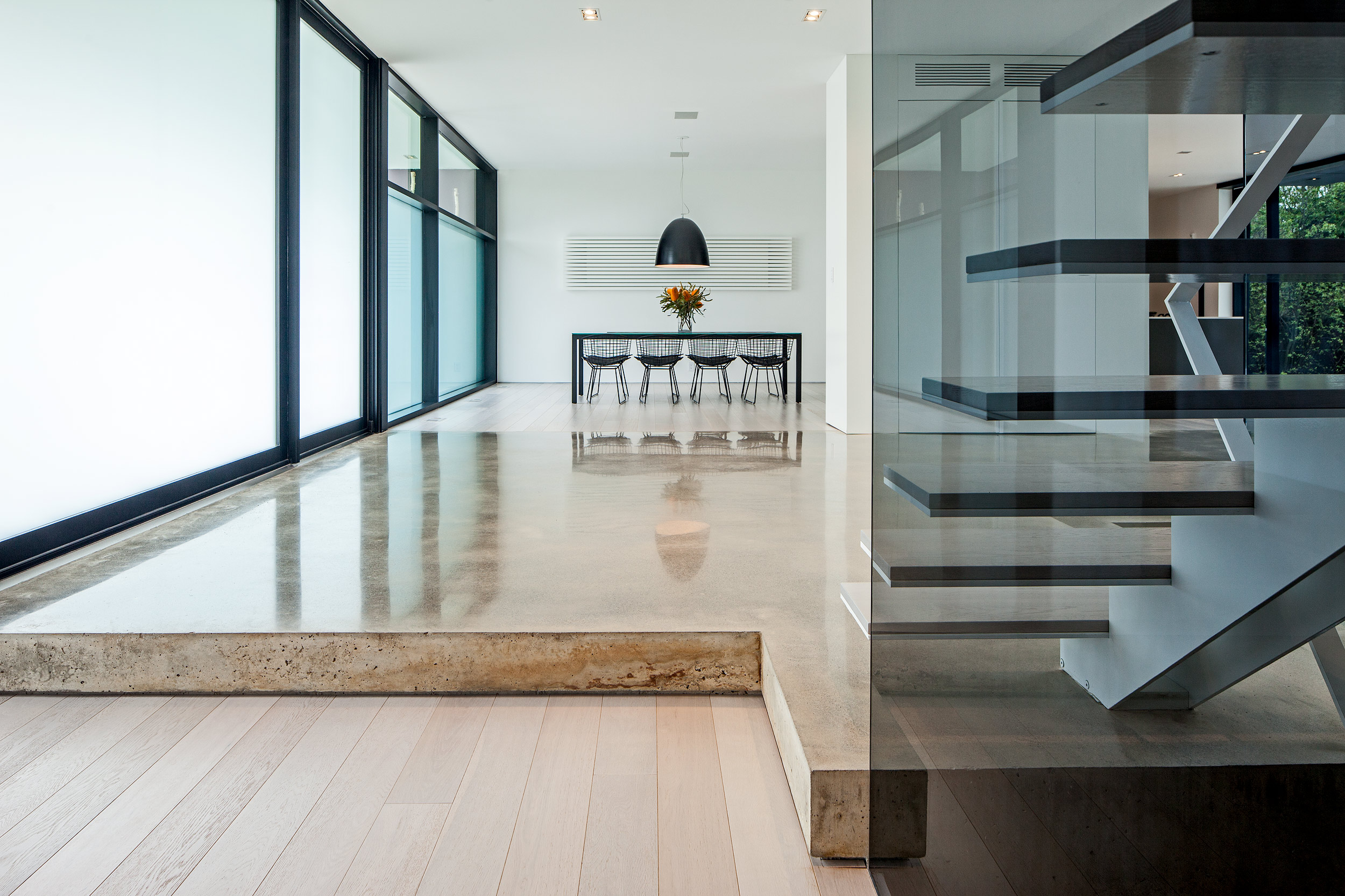 Architectural interior of a modern home floating staircase hardwood and concrete floors