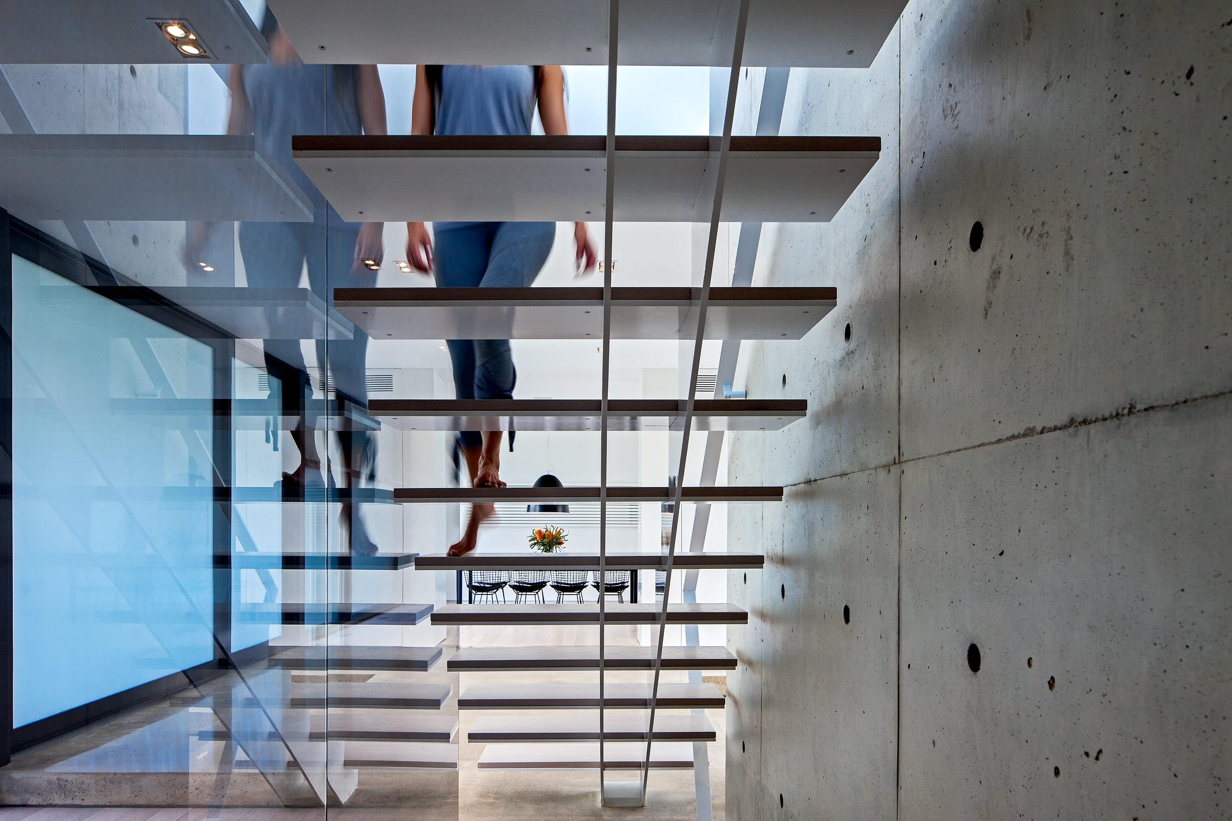 A woman walking up a floating staircase in an ultra modern home architectural photography by Peter A. Sellar