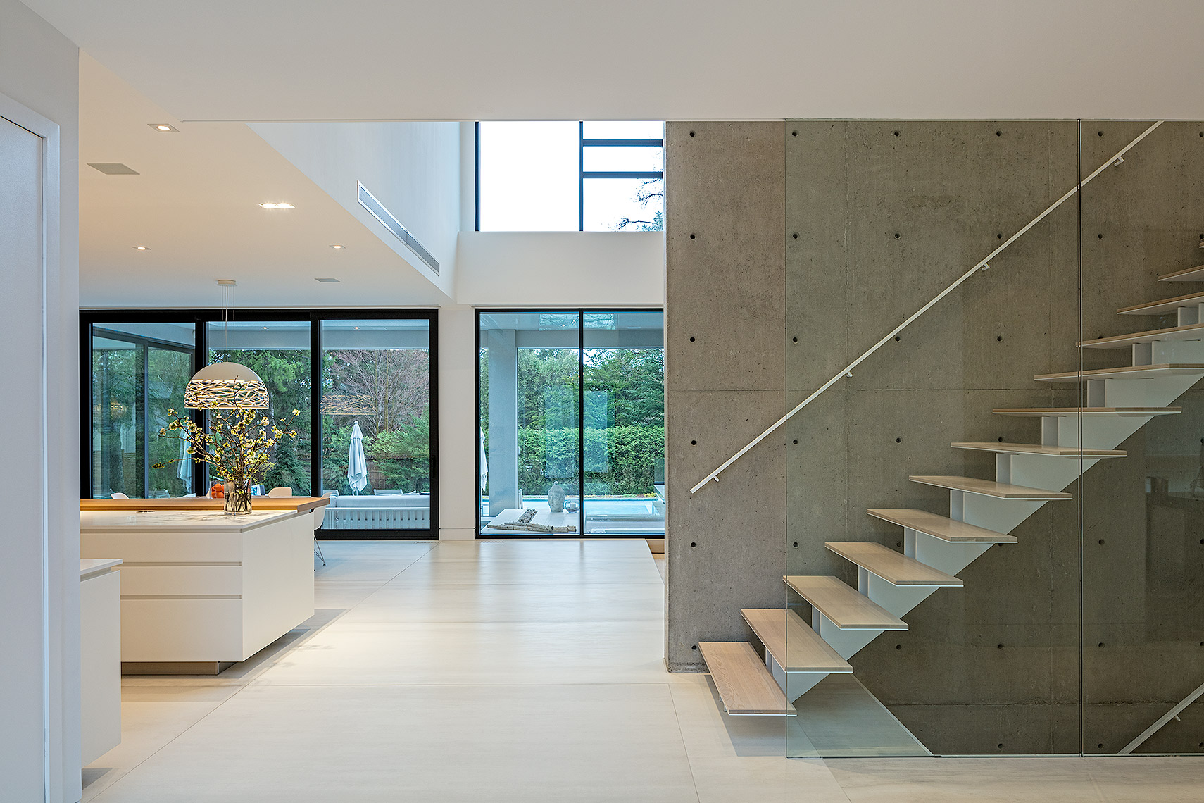 Floating staircase with concrete and glass walls looking in to the kitchen